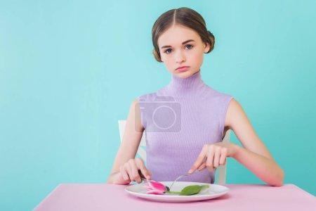 beautiful teen girl on diet eating tulip flower