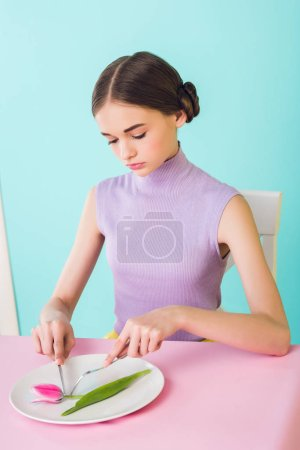 elegant teenager eating pink tulip flower, diet concept