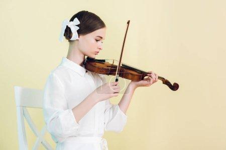 Photo pour Belle jeune musicienne en tenue blanche jouant du violon, isolée sur jaune - image libre de droit