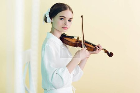 beautiful teenager in white outfit playing violin, isolated on yellow