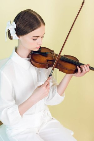 teen musician in white outfit playing violin, isolated on yellow
