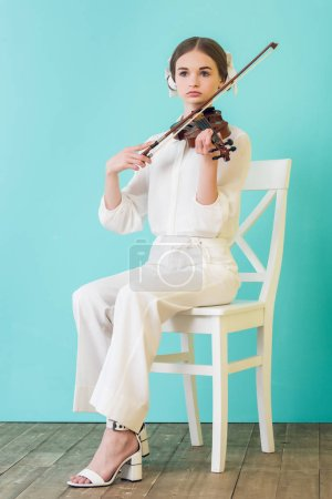 attractive teen musician playing violin and sitting on chair, on blue