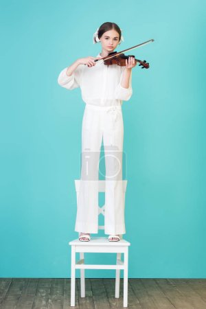 teen girl playing violin and standing on chair, on blue
