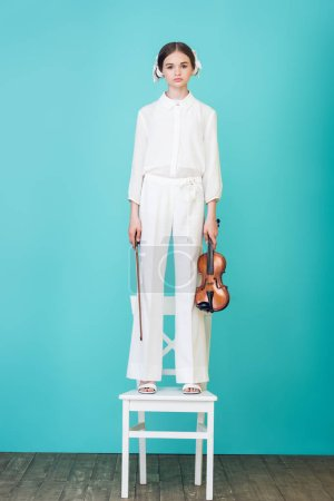 girl in white outfit holding violin and standing on chair, on blue
