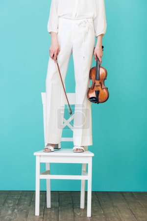 cropped view of girl holding violin and standing on chair, on blue