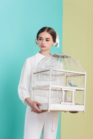 attractive girl in trendy white outfit with parrot in cage, on turquoise and yellow