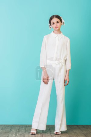 fashionable teen girl posing in white outfit on turquoise