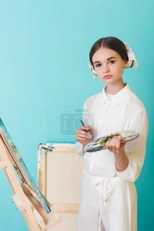 Photo pour Mise en plis chez les adolescentes artiste peinture sur chevalet avec pinceau et palette, sur turquoise - image libre de droit
