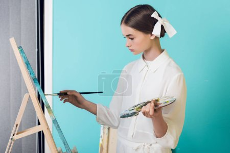 fashionable youth artist painting on easel with brush and palette, on turquoise