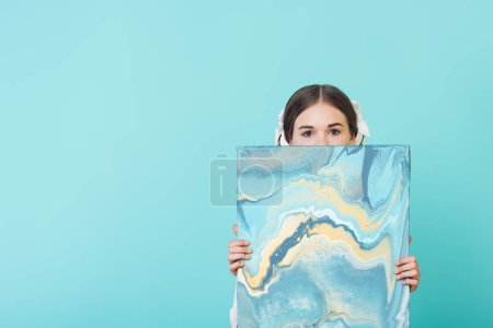 Photo for Fashionable youth girl holding blue oil painting, isolated on turquoise - Royalty Free Image
