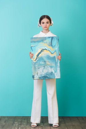 fashionable teenager holding abstract oil painting, on turquoise