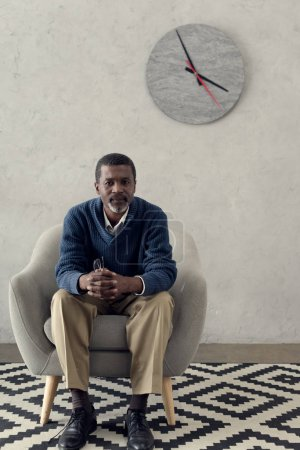 mature african american man sitting on armchair in room with clock