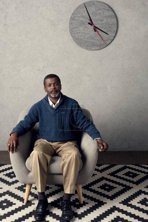 Photo pour Bel homme afro-américain assis sur le fauteuil dans la chambre avec horloge - image libre de droit