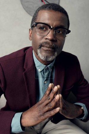 portrait of thoughtful fashionable african american man in trendy eyeglasses