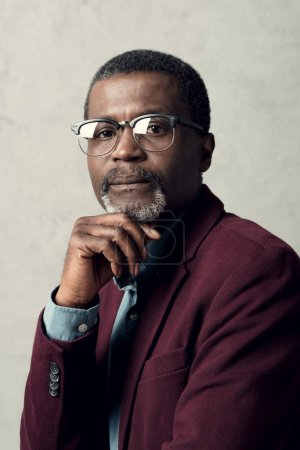 Photo for Portrait of pensive african american man in trendy eyeglasses and burgundy jacket - Royalty Free Image