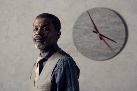 portrait of stylish african american man in waistcoat with clock on wall