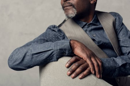 cropped view of stylish african american man in waistcoat sitting in armchair