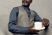 cropped view of stylish african american man in waistcoat holding cup of coffee