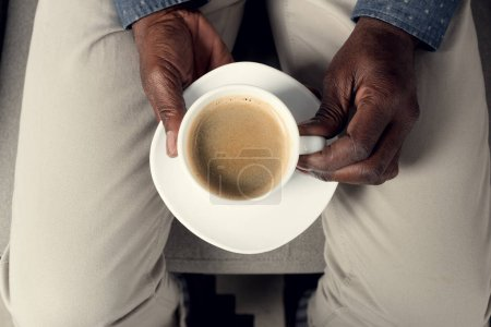 partial top view of african american man holding cup of coffee