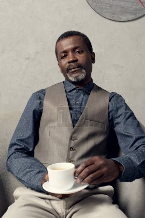 confident stylish african american man sitting in armchair with cup of coffee