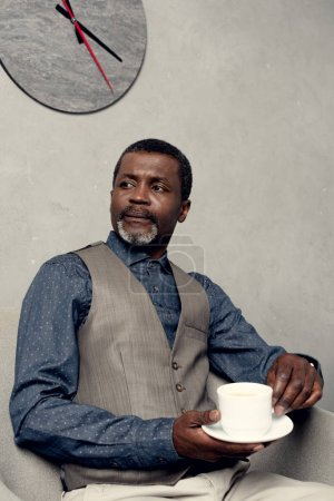 serious african american man in waistcoat sitting in armchair with cup of coffee