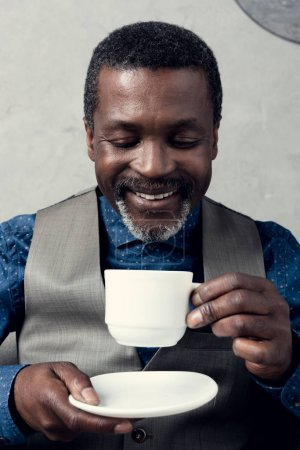 portrait of smiling african american man in waistcoat with coffee cup