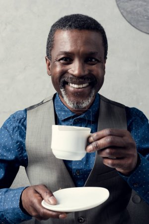 portrait of cheerful african american man with cup of coffee