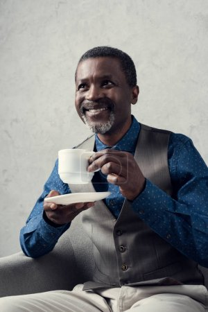 happy stylish african american man with cup of coffee sitting in armchair