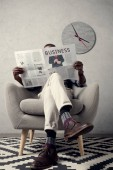 stylish african american man reading business newspaper while sitting in armchair with clock on wall