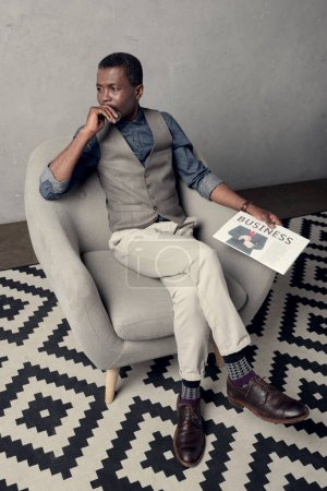 stylish african american man in waistcoat sitting in armchair with business newspaper