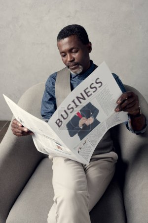 middle aged african american man reading business newspaper while sitting in armchair