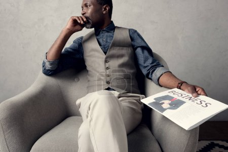 thoughtful african american man sitting in armchair with business newspaper