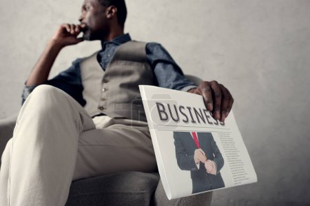 selective focus of pensive african american businessman holding business newspaper