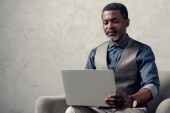 confident african american businessman with laptop sitting in armchair