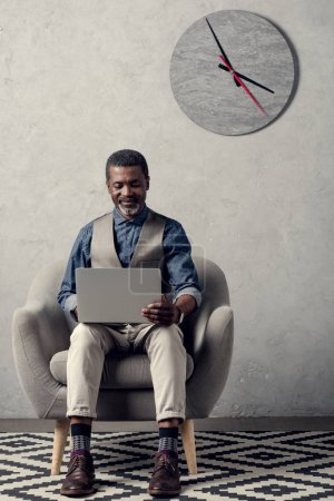 mature african american businessman with laptop sitting in armchair in office with clock on wall