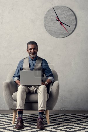 smiling african american businessman using laptop in armchair in office with clock on wall
