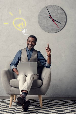 executive african american businessman with laptop having idea and pointing up, with light bulb sign