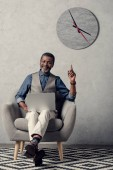 stylish african american businessman pointing up and using laptop in office with clock on wall