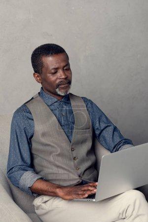 serious mature african american businessman using laptop at work