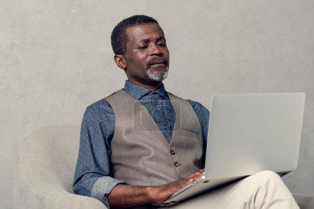 mature stylish african american businessman using laptop at work