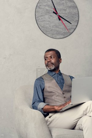 stylish african american businessman using laptop in office with clock on wall