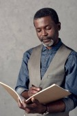 confident african american businessman writing in planner
