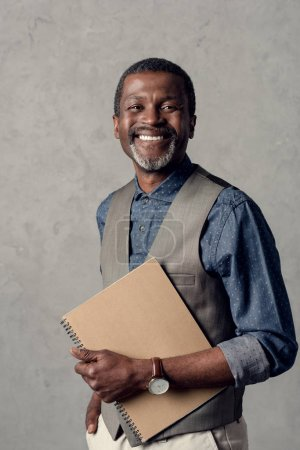 handsome smiling african american businessman with planner