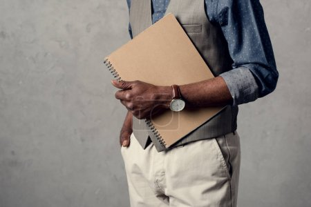cropped view of african american businessman holding planner