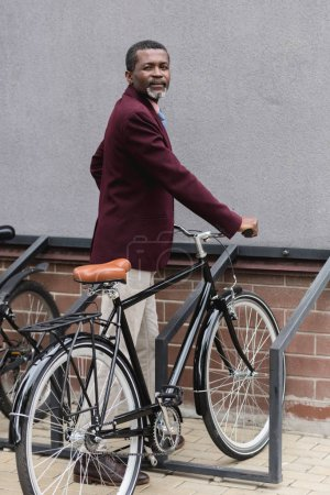 middle aged african american man with bike on parking for bicycles