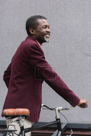 stylish smiling african american man in burgundy jacket posing near bicycle