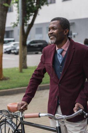 Photo pour Souriant afro-américain dans la veste tendance de Bourgogne à vélo en ville - image libre de droit