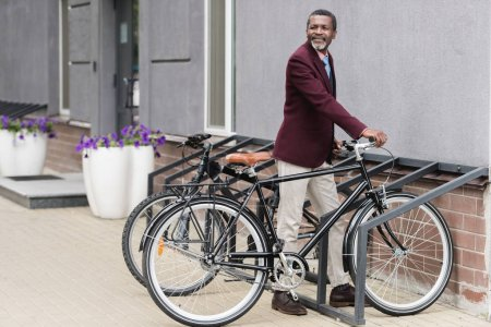 trendy african american businessman with bike on parking for bicycles