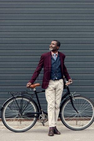 stylish mature african american man in burgundy jacket posing near bicycle