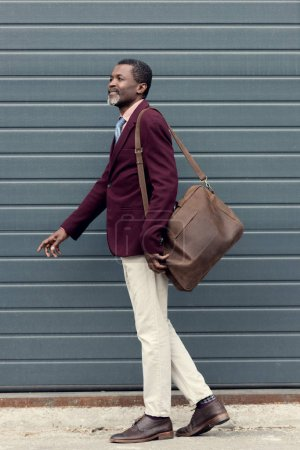 stylish mature african american man posing in trendy burgundy jacket with leather bag